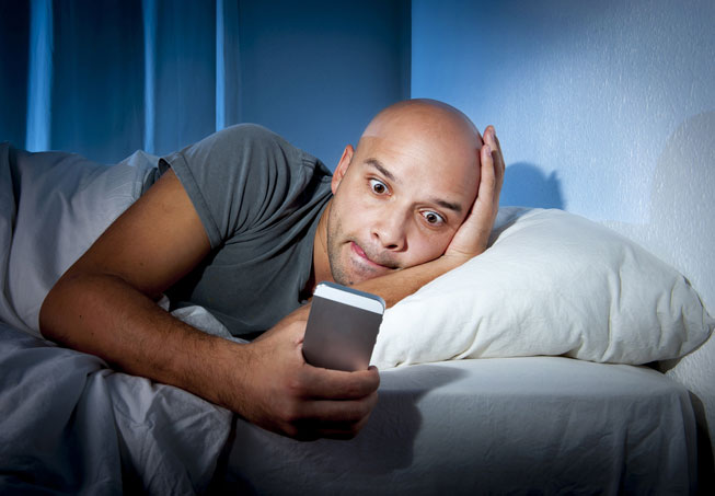 Bald Man Lying in Bed Looking at his Smart Phone Late at Night