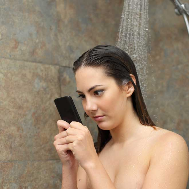 Girl checking her phone while taking a shower
