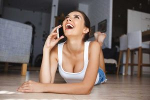 Young woman on the phone laughing in response to pick up line